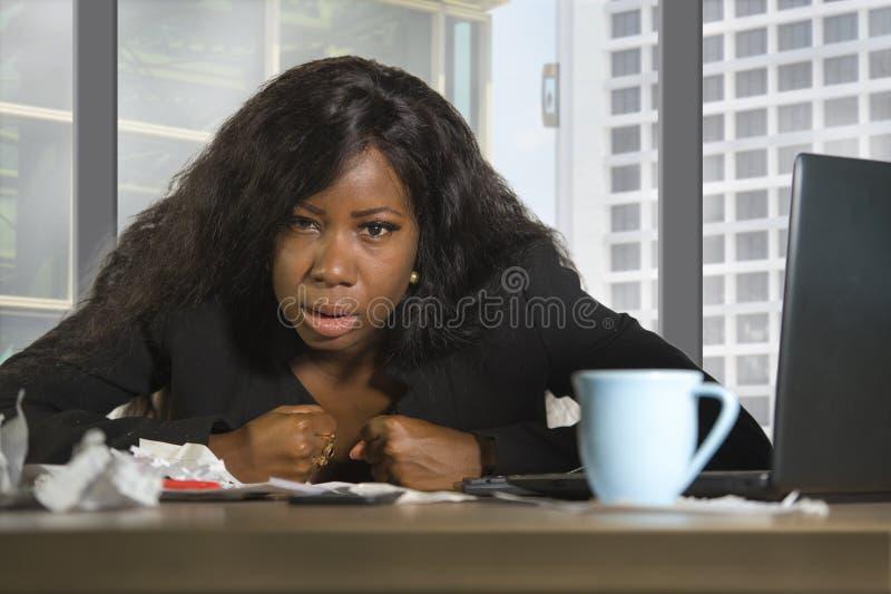 Осадка детенышей вымотанная и отжатая черная Афро-американская бизнес-леди деятельности и унылых на столе компьютера офиса окном  стоковое фото rf