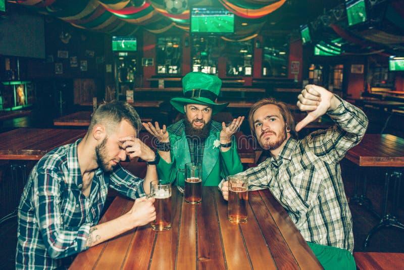 Осадка и несчастные молодые люди сидят на таблице в пабе Они имеют кружки пива Человек в костюме среднего St. Patrick носки стоковое изображение