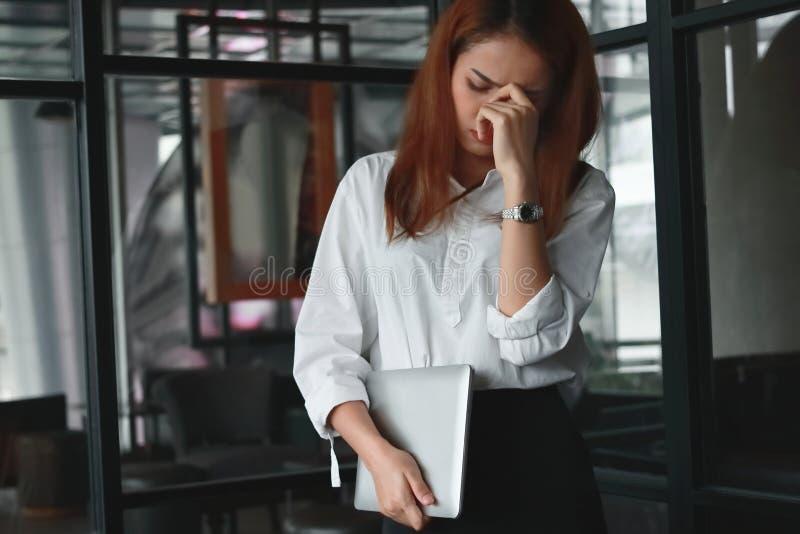 Осадка усилила азиатское положение и чувство бизнес-леди разочарованное или утомлянное в офисе стоковые фото