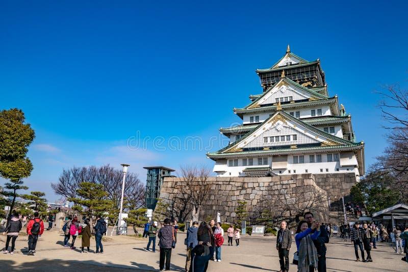 Осака, Япония - 4-ое марта 2018: Японец, туристы, путешественники шел вокруг замка Осака в марте 2018 с сухим деревом вокруг, Oas стоковое изображение