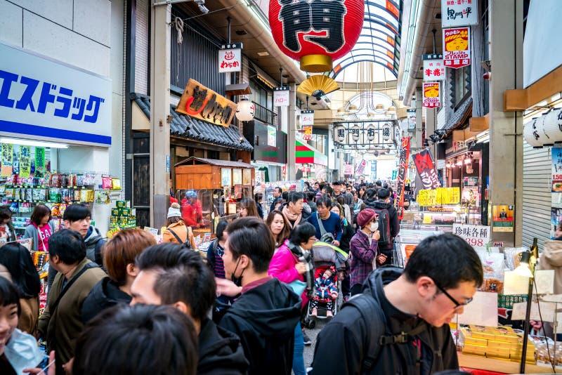 Осака, Япония - 3-ье марта 2018; Японские местные люди, туристы и путешественники идя и есть на рыбном базаре рынка Kuromon Ichib стоковое изображение
