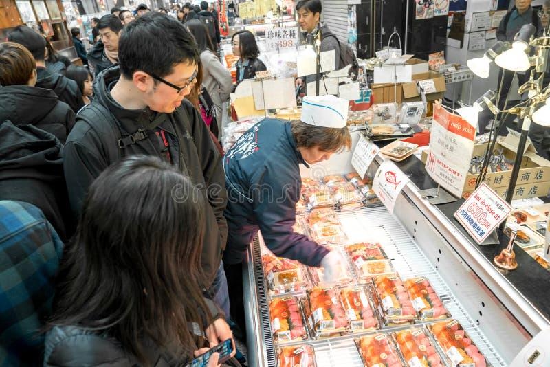 Осака, Япония - 3-ье марта 2018; Японские местные люди, туристы и путешественники идя и есть на рыбном базаре рынка Kuromon Ichib стоковое фото