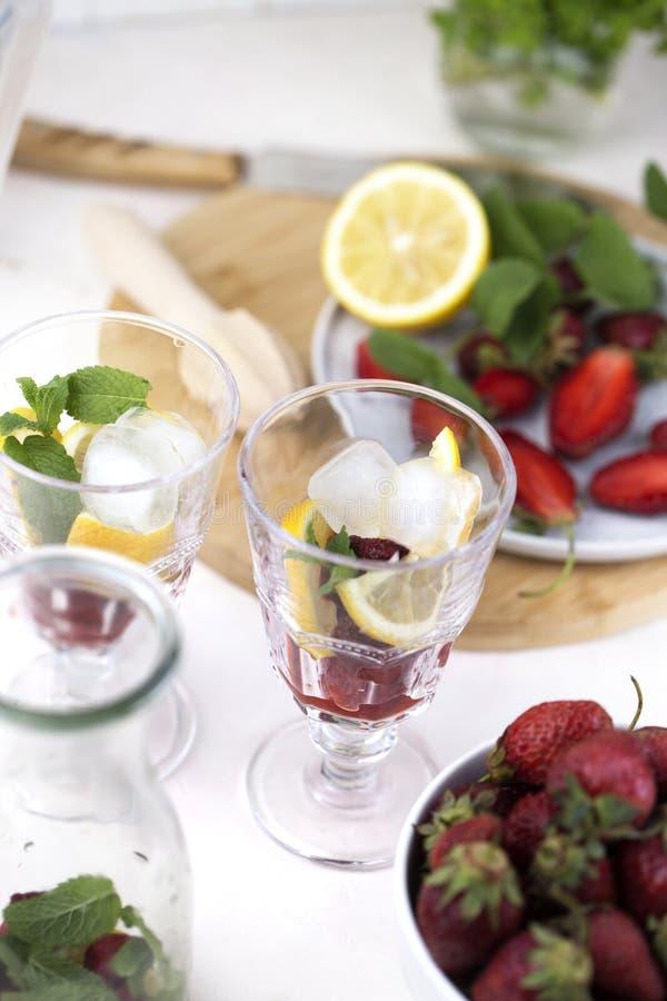 Освежающие напитки на лето, холодный сок Olorful лимонада клубники в стеклах с кубами льда стоковые изображения rf