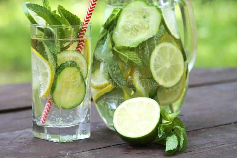 Освежая вода холодных напитков лета Sassy с лимоном, известкой, огурцом, мятой, имбирем в стекле и кувшином на деревянном столе,  стоковое фото