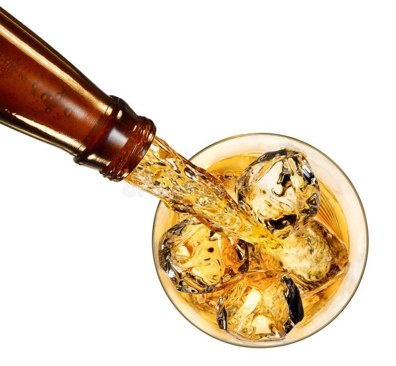 Освежая золотой яблочный сидр лить в стекло с кубами льда Взгляд крупного плана надземный на белизне стоковые фотографии rf