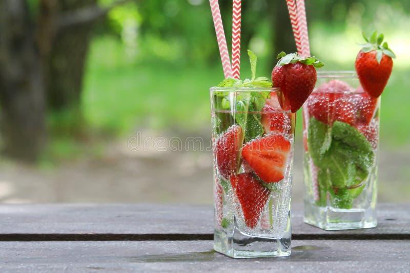 Освежая клубника холодных напитков лета с мятой в стекле на деревянном столе, на открытом воздухе стоковое изображение rf