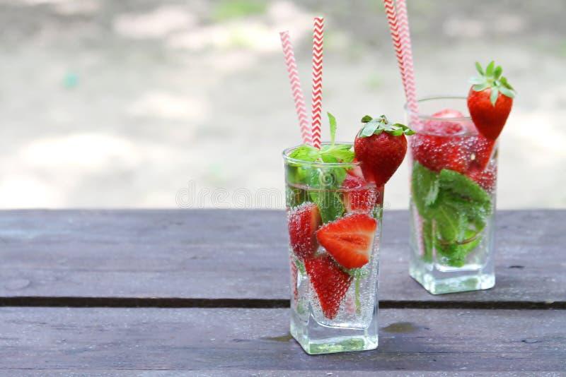 Освежая клубника холодных напитков лета с мятой в стекле на деревянном столе, на открытом воздухе стоковые фотографии rf
