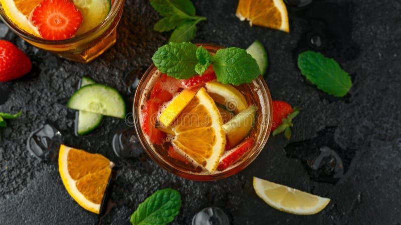 Освежая коктейль Pimms с фруктом и овощем на деревенской черной таблице стоковое изображение