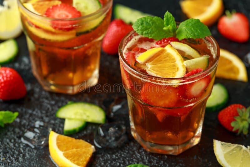 Освежая коктейль Pimms с фруктом и овощем на деревенской черной таблице стоковое фото