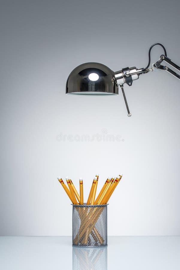 Освещать вверх по оранжевым канцелярским принадлежностям держателя карандаша с лампой стола стоковые фотографии rf