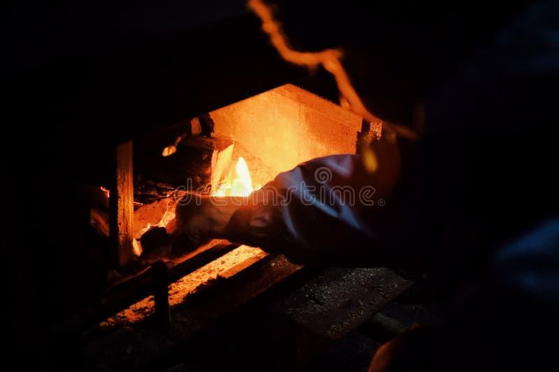 освещение молодой женщины вверх по огню в традиционном камине во время холодных зимних месяцев стоковое изображение