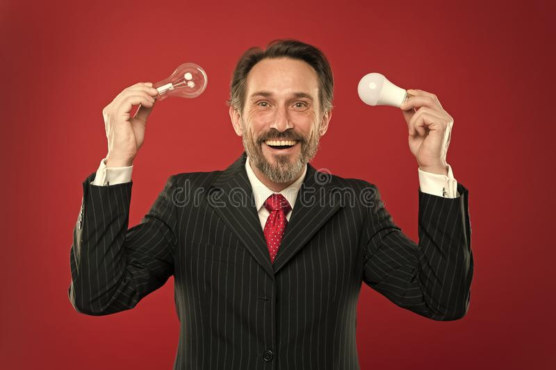 Освещение энергии эффективное Освещать выборы для сохранения денег Электрическая лампочка владением костюма бородатого консультан стоковая фотография rf