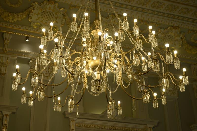 Освещенная золотая люстра, декоративный винтажный потолок стоковые фото