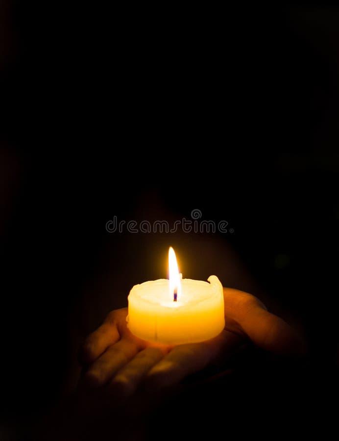 Освещенная свеча в руке ` s женщины стоковое изображение