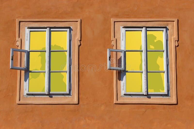 Освещенные окна квартиры с силуэтами романтичных людей, концепции дня Святого Валентина, романтичного человека держа розу и пару стоковое изображение