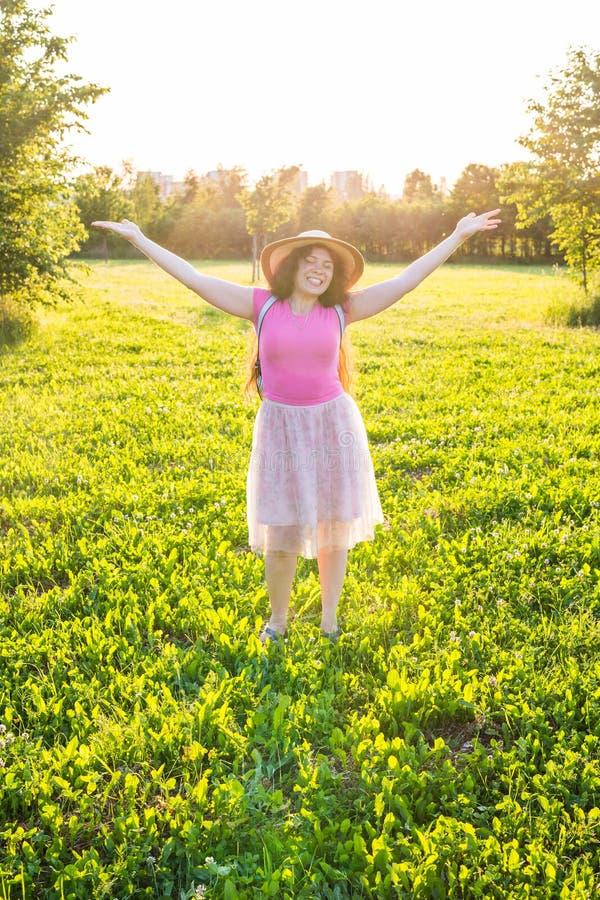Освободите счастливые оружия повышения молодой женщины наблюдая солнце на заднем плане на восходе солнца стоковое изображение