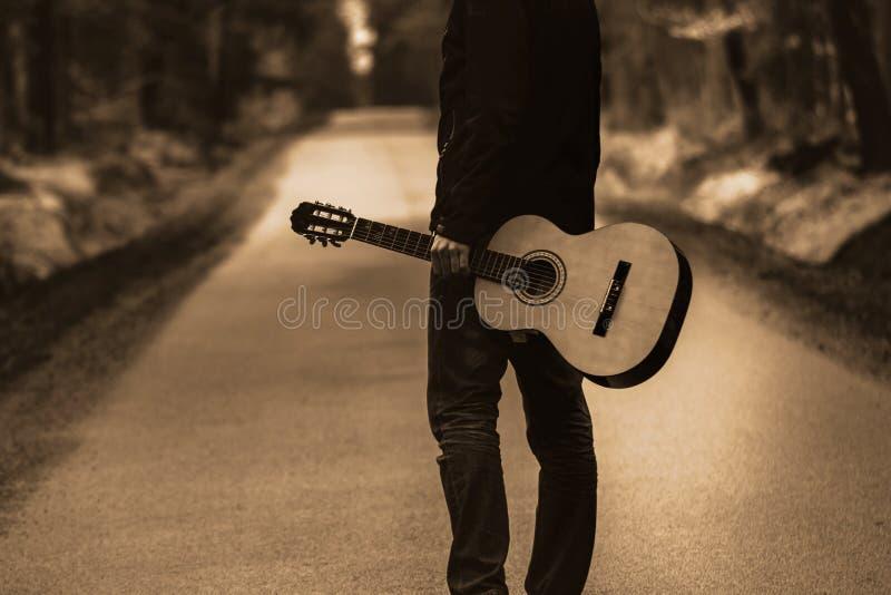 Освободите перемещение с аппаратурой страны, гитарой в лесе стоковое фото rf