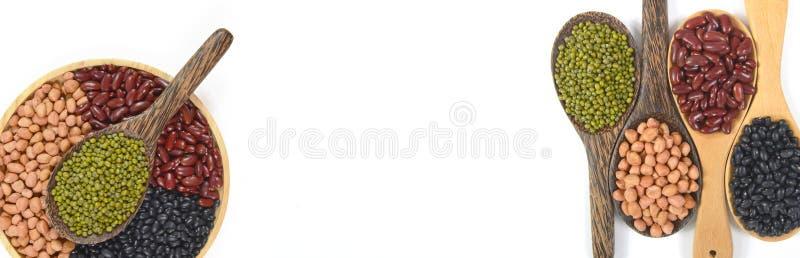 Осеменяет фасоль beansBlack, красную фасоль, арахис и фасоль Mung полезную для здоровья в деревянных ложках на белой предпосылке  стоковое изображение rf