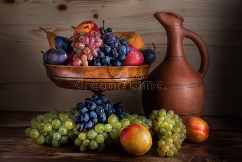 Осенний натюрморт плодоовощ с грузинским кувшином на деревенской деревянной плате стоковое фото