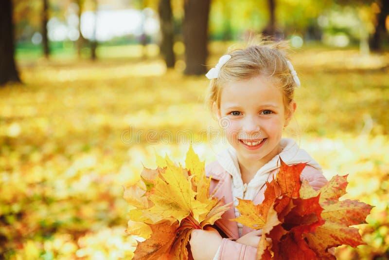 Осенний портрет милой кудряшки Маленькая забавная девушка, играющая с желтыми листьями в лесном ребенке, прогуливаясь по улице стоковая фотография rf