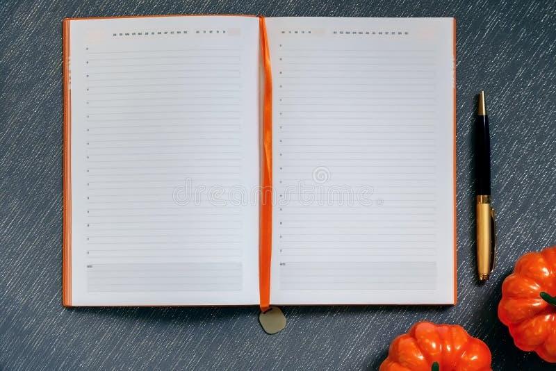 Осенняя полоса с макетом Пустой блокнот с пустой страницей, ручкой, оранжевыми тыквами, хэллоуин рутина на серо-голубом фоне стоковое фото rf
