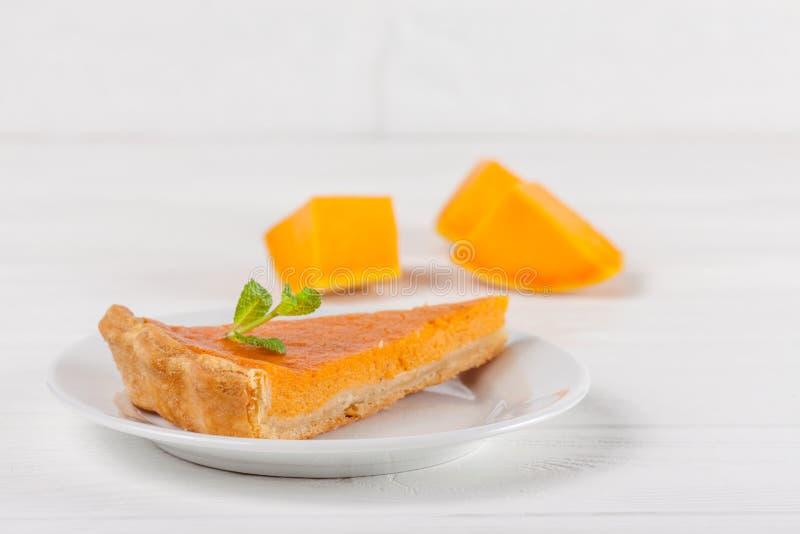 Осень десерта пирога тыквы домодельная очень вкусная Часть традиционного торта с отрезанной тыквой на белой деревянной предпосылк стоковое изображение