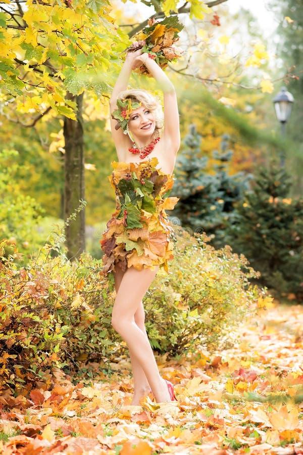 Осень, женщина в платье с листьями в парке Октябрь, стоковые фото