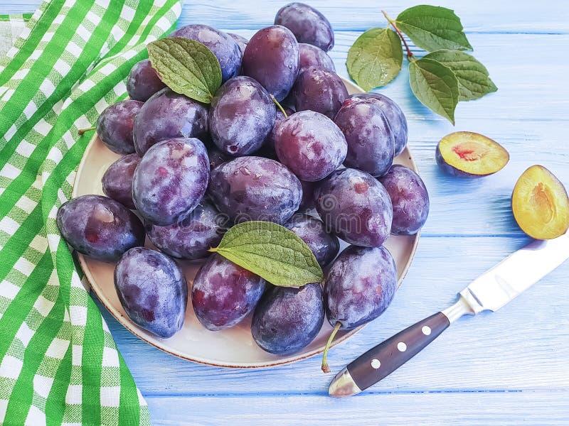 Осень очень вкусная на таблице плиты, голубая деревянная предпосылка свежего органического сочного витамина сливы десерта естеств стоковое изображение rf