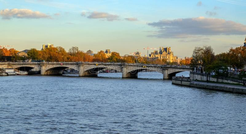 осень paris Солнце освещает реку Сену, повернутые желтые деревья на берег и красивые дома которое делают архитектурноакустический стоковое изображение rf