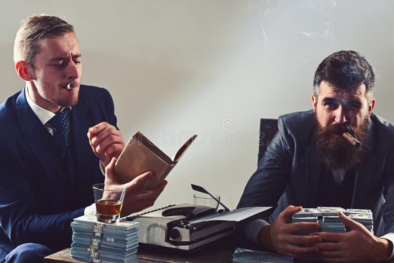 Ослабленное чувство Успешный вклад в деле Бизнесмены пишут финансовый отчет пока выпивающ и курящ стоковое фото rf