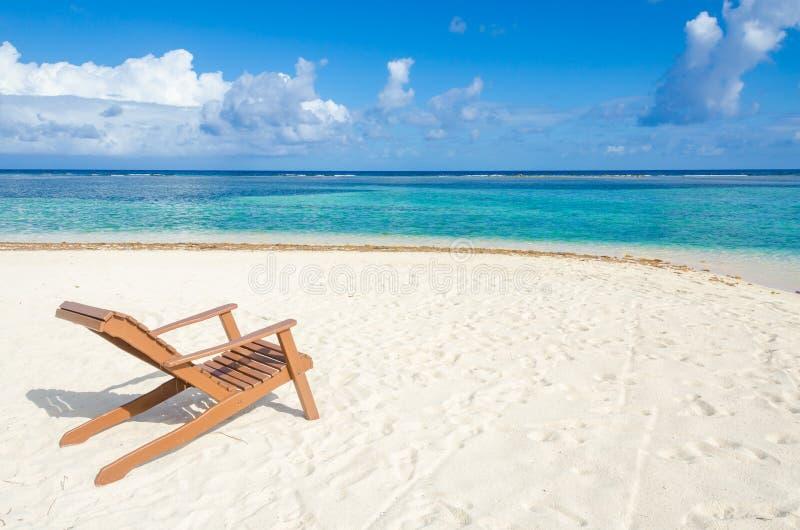 Ослабляющ на стуле - Белизе Cayes - небольшой тропический остров на барьерном рифе с пляжем рая - известный за нырять, и стоковые изображения rf