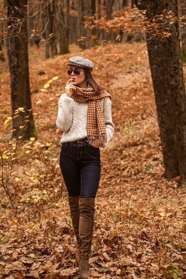 Ослабляя курение Женщина наслаждается курить самостоятельно Сиротливый курильщик Осень здесь Милая женщина в курении шляпы и солн стоковое фото
