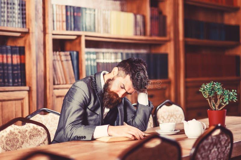 Ослабьте, отдых, время чая Зрелый человек сидит в стильное внутреннем и наслаждается расслабляющим чтением Бородатый человек в оф стоковые фотографии rf