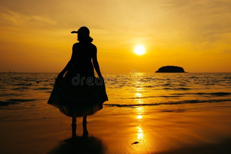 Ослабьте положение женщины на силуэте захода солнца моря пляжа стоковая фотография