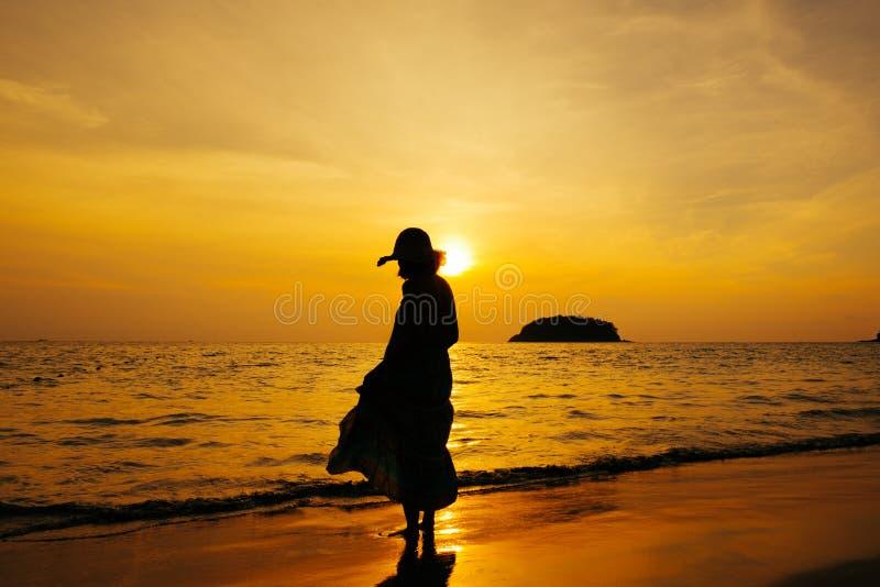 Ослабьте положение женщины на силуэте захода солнца моря пляжа стоковая фотография rf