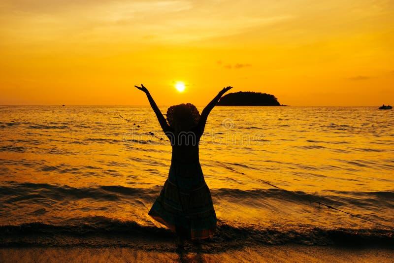 Ослабьте положение женщины на силуэте захода солнца моря пляжа стоковые фотографии rf