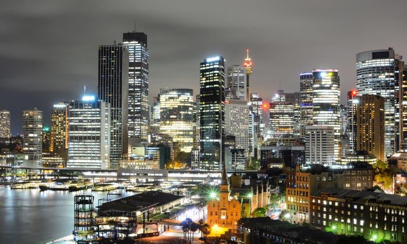 Ослеплять взгляд городского пейзажа ночи горизонта финансового района Сиднея центрального и круговой набережной стоковые фото