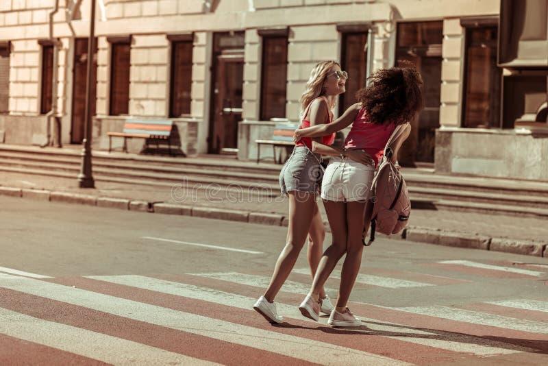 Ослепляя дама обнимая с ее девушкой пока идущ улицы стоковое изображение rf