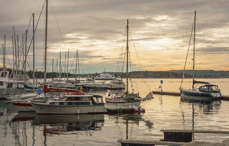Осло, Норвегия - маленькие лодки в Марине - желтые небеса стоковые изображения