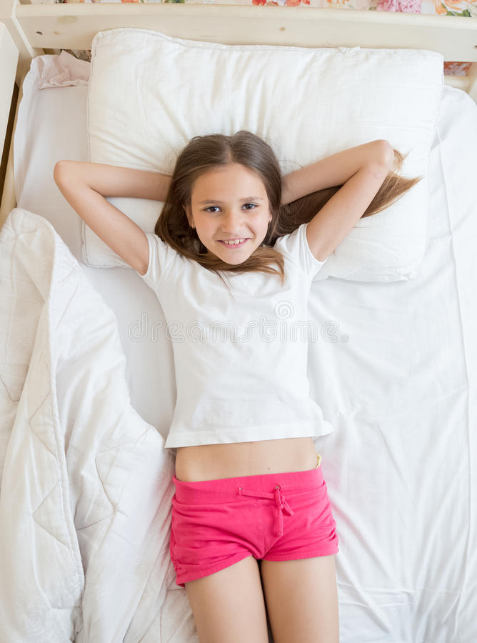 Осмотрите сверху на милой девушке лежа на кровати и смотря камеру стоковое изображение rf