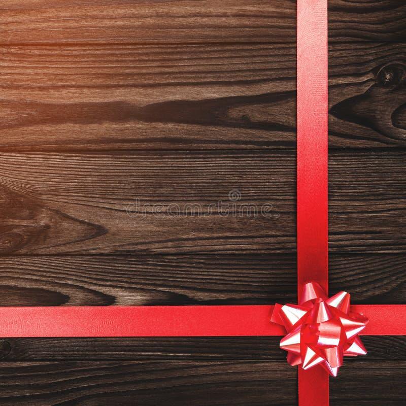 Осмотрите сверху с Рождеством Христовым надписи на предпосылке темного коричневого цвета деревянной с красной лентой стоковые изображения