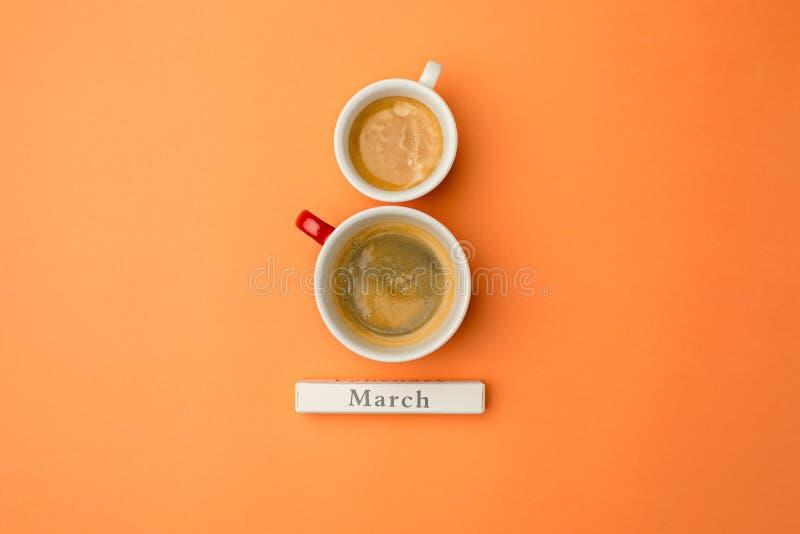 Осмотрите сверху с 2 чашками кофе с космосом экземпляра Предпосылка на день женщины, 8-ое марта померанцовая таблица стоковое фото rf