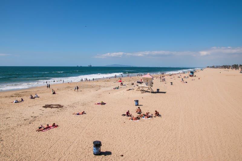 Осмотрите сверху широкий песчаный пляж Huntington Beach Калифорния показывая sunbathers пловцов и серферов стоковые изображения