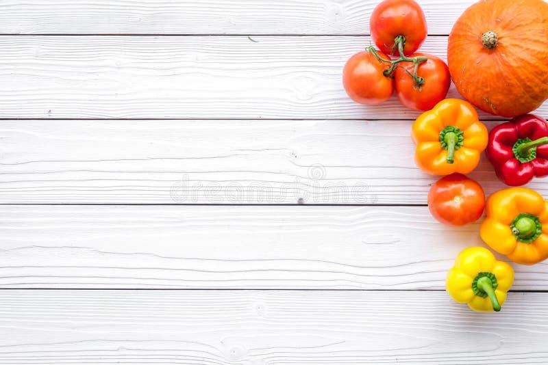 Основание здорового питания Овощи тыква, паприка, томаты на белом деревянном copyspace взгляд сверху предпосылки стоковое фото rf