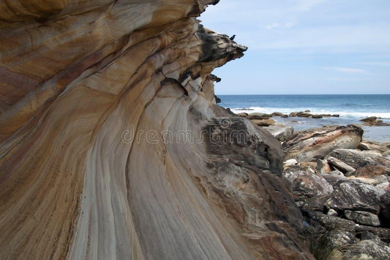 Основание скалы на пляже Marley смотря вне к морю стоковое фото rf