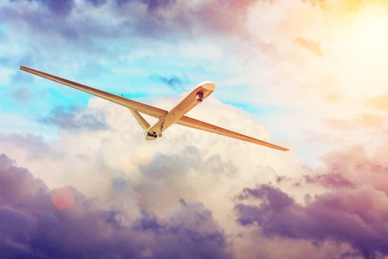 Оставлятьый без людей трутень военных самолетов летает на небо облаков захода солнца стоковое фото rf