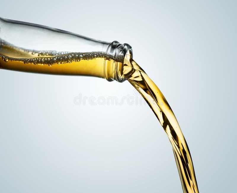 Остановите крупный план действия янтарного пива лить от ясной бутылки стоковые фото