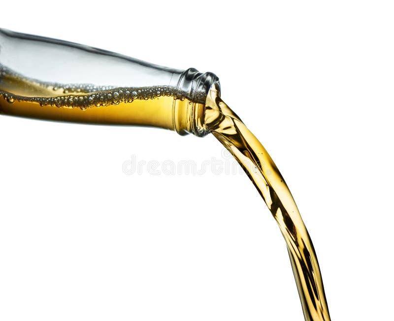 Остановите крупный план действия янтарного пива лить от ясной бутылки стоковые изображения rf