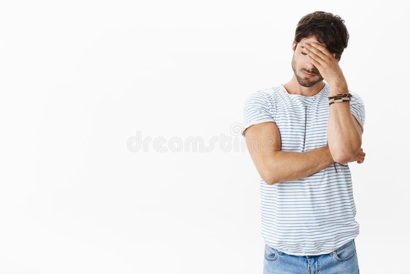 Остановите меня уставший слушая лож Портрет неловкого вымотанного и, который стекаенного красивого молодого человека в striped фу стоковое фото rf