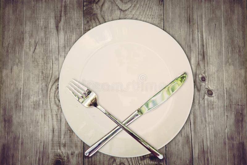 Остановите съешьте концепцию Деревянный стол при пустая плита и пересеченный серебряный столовый прибор символизируя для того что стоковые изображения